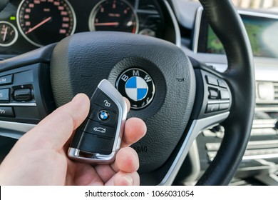Sankt-Petersburg Russia, April 4, 2018: Man's hand holding a wireless BMW X5 F15 car key in black leather interior. Modern Car interior details. Car detailing. Car inside.