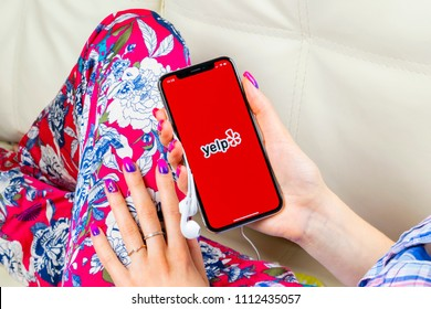 Sankt-Petersburg, Russia, June 8, 2018: Yelp application icon on Apple iPhone X screen close-up in woman hands. Yelp app icon. Yelp.com application. Social network. Social media