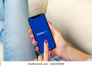 Sankt-Petersburg, Russia, May 30, 2018: Booking.com application icon on Apple iPhone X screen close-up in woman hands. Booking app icon. Booking.com.  Social media app. Social network