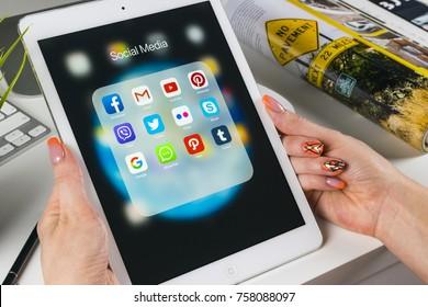 Sankt-Petersburg, Russia, November 14, 2017: Woman Hands using iPad pro with icons of social media facebook, instagram, twitter, google application on screen. Smartphone Starting social media app.