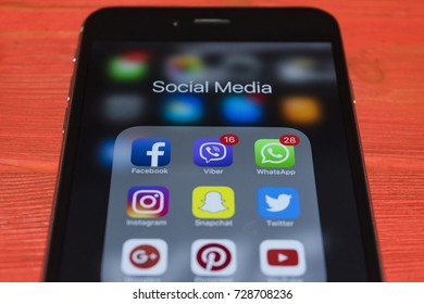 Sankt-Petersburg, Russia, October 2, 2017: iphone 7 plus with icons of social media on screen on red wooden desk. Smartphone life style smartphone. Starting social media app.