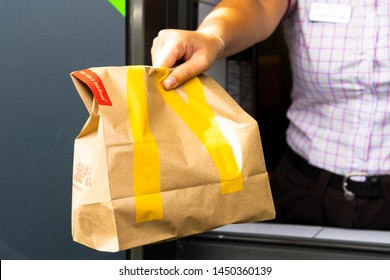 Sankt-Petersburg/Russia - July 11 2019: McDonald's worker holding bag of fast food. Hand through the window of mcdonalds car mcauto.