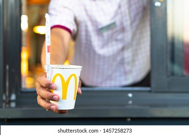 Sankt-Petersburg/Russia - July 21 2019: McDonalds worker holding cup with coca-cola. Hand with a paper cup with a straw through the window of mcdonalds car drive thru service.