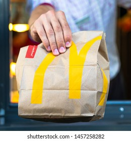 Sankt-Petersburg/Russia - July 21 2019: McDonalds worker holding bag of fast food. Hand with a paper bag through the window of mcdonalds car drive thru service.
