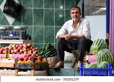 SANLIURFA, TURKEY - AUGUST 21, 2009 : A green grocer selling apples, cucumbers and watermelons sits in his store at the Urfa (Sanliurfa) bazaar in Urfa in eastern Turkey.