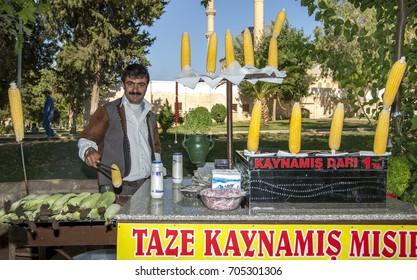 SANLIURFA, TURKEY - JULY 06, 2010 : A man working at his corn cob stall at Ayn-i Zeliha, the second sacred pool in Golbasi Park in Sanliurfa in eastern Turkey.