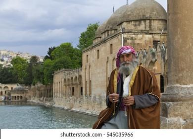 "SANLIURFA, TURKEY - MAY 13, 2015: Turkish man in local costumes looks at me, in the park  known as ""Abrahams Pond"" or ""Balikligol"" in Sanliurfa, Turkey."