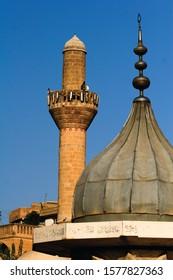 Sanliurfa / Turkey-23 October, 2007: View on minaret and dome on blue sky background. Urfa city. Holy lake Balikli Gol (Fish Lake). Religion, faith, Islam, history, tourism concepts. Vertical close-up