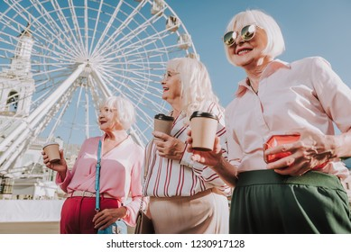 Sanny day. Waist up portrait of friendly meeting of three stylish older women holding coffee with ferris wheel on background
