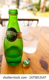 sanpedro, malaga/spain - 08 10 2019: Perrier brand sparkling water with glass and ice on wooden table, refreshing healthy drink.