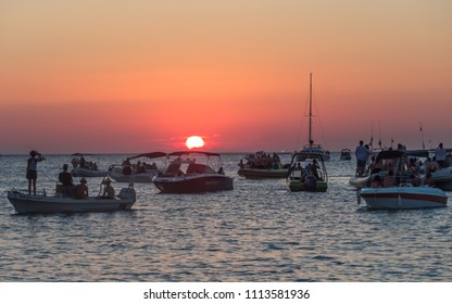 Sant Antoni de Portmany, Balearic Islands, Spain - July 10, 2017: Sunset at Café del Mar. People on boats gathered to see the sunset.