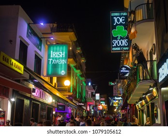 Sant Antoni de Portmany, Ibiza / Spain - July 12, 2017: Walking people at summer night. Street Carrer de Santa Agnes, glowing colored signboards of numerous bars and pubs.