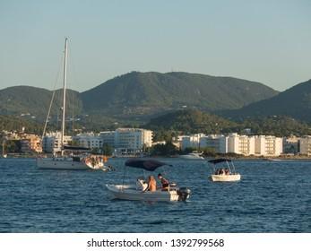Sant Antoni de Portmany, Ibiza, Spain - July 10, 2017: Yacht and boats with riders near Ibiza island coast. Green wooded slopes of the island, hotels shore.