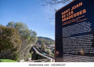 SANT JOAN DE LES ABADESSES,SPAIN- OCTOBER 25,2018: Old bridge and display sign information village name.