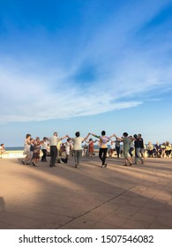 Sant Pol de Mar, Catalonia, August 2019: A group of locals dancing sardanas by the sea. The sardana is a musical genre typical of Catalan culture and danced in circle following a set of steps.