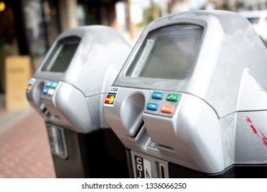 Santa Ana, California/United States - 03/10/19: A closeup of a pair of parking meters with credit card payment option and colored buttons, and the logos of Visa and Mastercard accepted