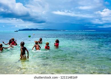 Santa Ana community, Solomon Islands-  December 17,2017 Happy melanesian   chidrens play  ball  in the  ocean, paradise tropical landscape background, Oceania, Melanesia