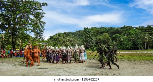 Santa Ana I, Solomon Islands - March 30 2014: A war-dance - mud covered marauders attack the women, and are driven off by the black painted men of the village (and a plucky kid)