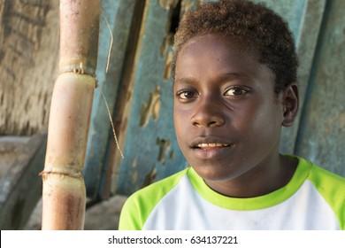 Santa Ana, Solomon Islands - March 6th, 2017: A melanesian boy portrait, looking at camera, Santa Ana, Solomon  Island.