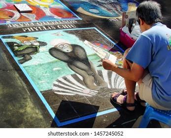 SANTA BARBARA, CALIFORNIA - MAY 30, 2004: Artist creating a chalk drawing at the I Madonnari Italian Street Painting Festival at the Santa Barbara Mission