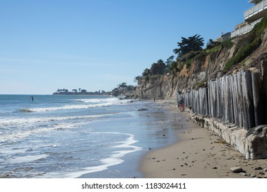 Santa Barbara, California / USA - March 4 2017: Sunny sandy beach shoreline, with houses on the cliff above along oceanside Del Playa Drive in Isla Vista