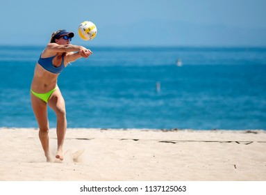 SANTA BARBARA, CALIFORNIA/USA - July 1, 2018: A female athlete prepares to serve during a beach volleyball tournament match on the sand next to ocean.