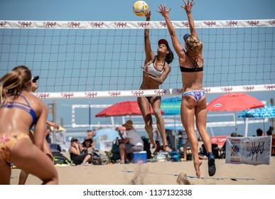 SANTA BARBARA, CALIFORNIA/USA - July 1, 2018: A women's beach volleyball player strikes the ball at the net during a tournament match. Opponent attempts block.