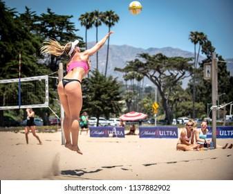 SANTA BARBARA, CALIFORNIA/USA - July 1, 2018: A women's beach volleyball player hits a jump serve during a tournament match.