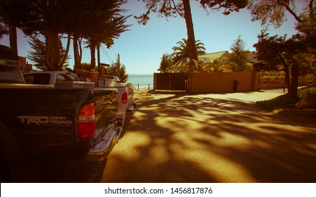 Santa Barbara, United States - February 25 , 2013 : In the shade and with palm trees around a pick up truck is parked next to the ocean with a play of shadow on the asphalt.