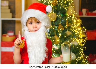 Santa boy in Santa hat. Funny child Christmas. Santa Claus - bearded funny child. Happy Santa Claus - little child boy with glass of milk and cookie. Christmas food and drink