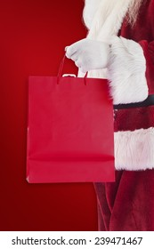 Santa carries red gift bag against red background