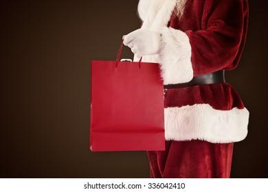 Santa carries red gift bag against dark brown background