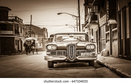 Santa Clara, Cuba - September 11, 2016: HDR - American red Ford Edsel classic car with white roof parked on the side street in Santa Clara Cuba - Retro Serie SEPIA Cuba Reportage