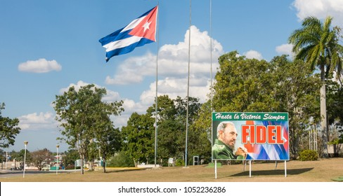 SANTA CLARA, CUBA-JANUARY 6, 2017: Poster with image of Fidel Castro and Cuban flag in the Revolution square in the city of Santa Clara, Cuba. Next is the Mausoleum of homage to Ernesto Che Guevara.