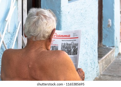 Santa Clara, Cuba-July 10, 2018: Shirtless Cuban senior man reading the Granma newspaper in the sidewalk. Granma is the official newspaper of the Communist Party in the island