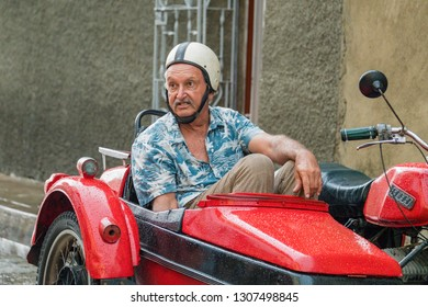 Santa Clara, Villa Clara, Cuba-January 27, 2019: Funny image of an old man in printed shirt sitting in a red side car. It is mandatory to use helmet while riding motorcycles in Cuba.