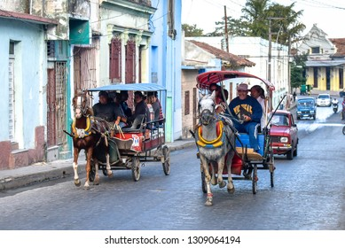 Santa Clara, Villa Clara, Cuba-January 4, 2019:  Two horse-drawn carriages full of commuters race up the hill in the Maceo street. Old houses are seen in the background.