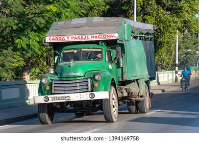 Santa Clara, Villa Clara, Cuba-May 5, 2019: Old vintage green truck driving on an urban road during the day. The Caribbean island is known for having many obsolete vehicles still working