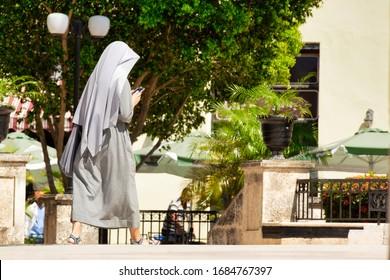 Santa Clara,Cuba- May 21 May 2018: Nun walking and looking at the mobile in the street