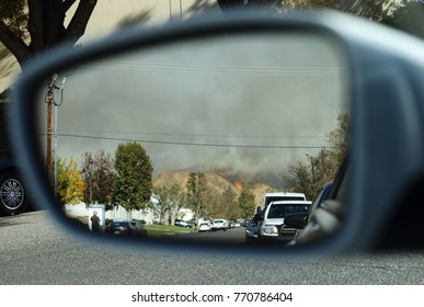 SANTA CLARITA, CA / USA - Dec. 5, 2017: Drivers wait in their vehicles for the chance to evacuate the area while the Creek Fire wildfire burns on the hillside behind them.