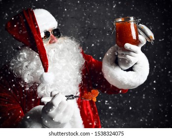 Santa Claus in aviator sunglasses is looking at a big jar of red salmon caviar, holding a full spoon of it under the snow. New year and Merry Christmas and happy holidays concept