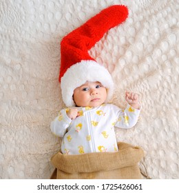 Santa Claus baby laying on bed in sack