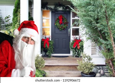 Santa Claus with a bag of Christmas presents approaches the front door of a beautifully decorated home.