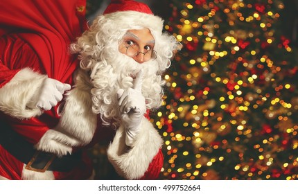 Santa Claus with a bag of gifts at the Christmas tree