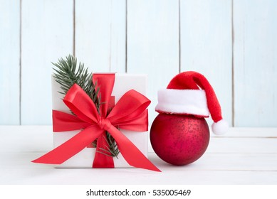 Santa claus ball with gift box and fir branch on vintage background with copy space