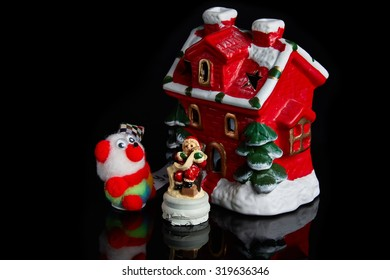 Santa Claus and bear near decorated house isolated on black