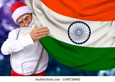 Santa claus with a beard holds a beautiful colored national flag of india state on fabric, concept of tourism, new year and christmas, economic and political prospects