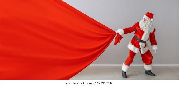 Santa Claus with big bag near light wall