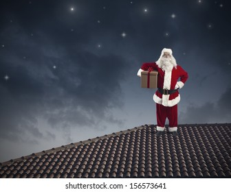 Santa Claus with a big present on a roof
