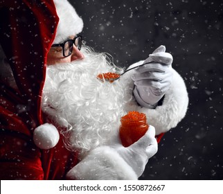 Santa Claus with a big white beard trying eating red caviar fish salmon looking at spoonful, holding a jar under the snow. New year and Merry Christmas and happy holidays concept